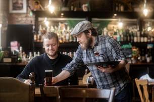 Barman serving beer to customer in traditional Irish public houseの写真素材 [FYI03616035]