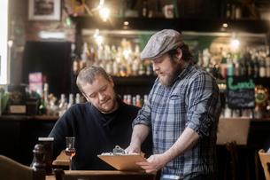 Barman looking at menu with customer in traditional Irish public houseの写真素材 [FYI03616036]