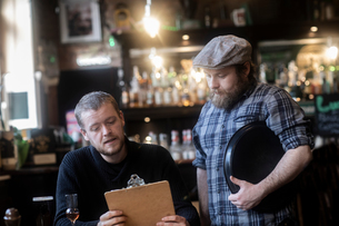 Barman serving customer  looking at menu in traditional Irish public houseの写真素材 [FYI03616037]