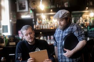 Barman serving customer  looking at menu in traditional Irish public houseの写真素材 [FYI03616037]