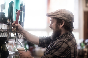 Barman pouring beer from pump in traditional Irish public houseの写真素材 [FYI03616040]