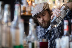 Barman pouring spirit bottle in traditional Irish public houseの写真素材 [FYI03616041]