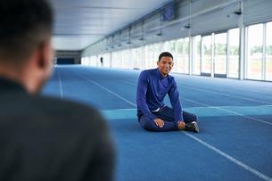 Runners sitting on indoor running trackの写真素材 [FYI03616189]