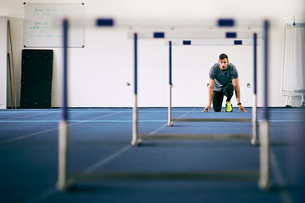 Athlete getting ready for hurdles on indoor running trackの写真素材 [FYI03616215]