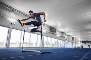 Athlete jumping over hurdle on indoor running trackの写真素材 [FYI03616217]