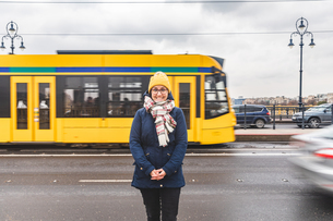 Woman posing on roadside, tram passing by in background, Budapest, Hungaryの写真素材 [FYI03616535]