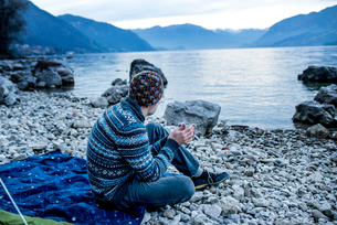 Man camping on lakeside, Onno, Lombardy, Italyの写真素材 [FYI03616551]