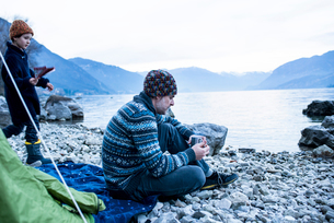Father and son camping by lakeside, Onno, Lombardy, Italyの写真素材 [FYI03616561]