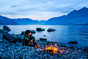 Boy by campfire at dusk, Onno, Lombardy, Italyの写真素材 [FYI03616574]