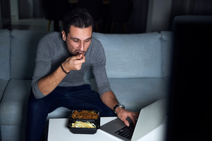 Young man sitting on sofa in evening eating takeaway and using laptopの写真素材 [FYI03616628]