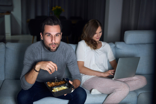 Young couple sitting on sofa in evening eating takeaway and using laptopの写真素材 [FYI03616629]