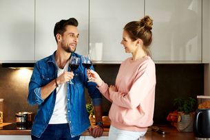 Couple talking and drinking red wine in kitchenの写真素材 [FYI03616662]