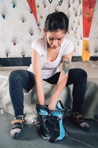 Woman getting climbing chalk from chalk bagの写真素材 [FYI03616686]