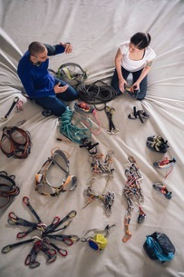 Climber friends on crash pad working with and learning about climbing equipmentの写真素材 [FYI03616693]
