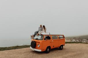 Young couple on top of recreational vehicle at coastal roadside, Jalama, California, USAの写真素材 [FYI03616773]