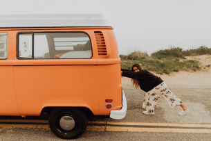 Young woman pushing recreational vehicle at coastal roadside, Jalama, California, USAの写真素材 [FYI03616774]