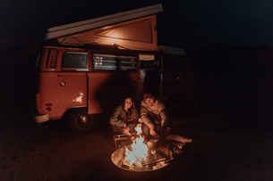 Young couple cooking camp fire by recreational vehicle at night, Jalama, California, USAの写真素材 [FYI03616775]