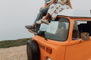 Young couple on top of recreational vehicle at coastal roadside, cropped, Jalama, California, USAの写真素材 [FYI03616776]