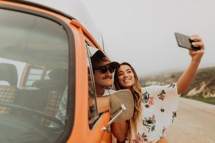 Young couple on roadside in recreational vehicle taking smartphone selfie,  portrait, Jalama, Califoの写真素材 [FYI03616782]