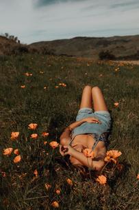 Young woman lying in field of wildflowers, Jalama, California, USAの写真素材 [FYI03616790]