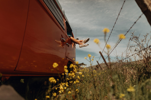 Young woman's legs out of recreational vehicle window on rural roadside, Jalama, California, USAの写真素材 [FYI03616797]