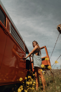 Young woman standing by recreational vehicle on rural roadside, Jalama, California, USAの写真素材 [FYI03616799]