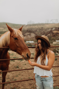 Young woman in felt hat feeding carrot to horse, Jalama, California, USAの写真素材 [FYI03616818]
