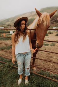 Young woman in felt hat feeding carrot to horse, Jalama, California, USAの写真素材 [FYI03616821]