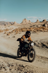 Motorcyclist riding in desert, Trona Pinnacles, California, USの写真素材 [FYI03616861]
