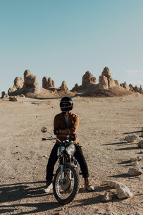 Motorcyclist on stationary bike, Trona Pinnacles, California, USの写真素材 [FYI03616862]