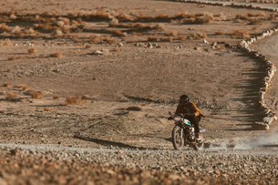 Motorcyclist riding in desert, Trona Pinnacles, California, USの写真素材 [FYI03616864]