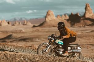 Motorcyclist riding in desert, Trona Pinnacles, California, USの写真素材 [FYI03616865]