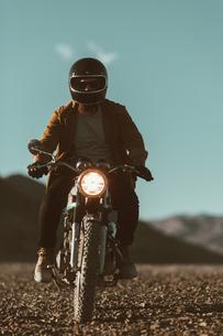 Motorcyclist riding in desert, Trona Pinnacles, California, USの写真素材 [FYI03616866]