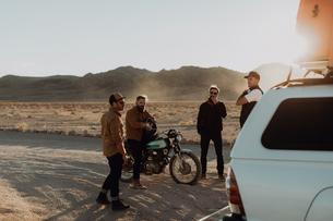 Motorcyclist friends taking break beside off road vehicle, Trona Pinnacles, California, USの写真素材 [FYI03616867]
