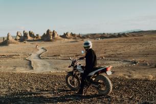 Motorcyclist on stationary bike, Trona Pinnacles, California, USの写真素材 [FYI03616868]