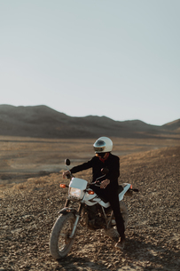Motorcyclist on stationary bike, Trona Pinnacles, California, USの写真素材 [FYI03616873]
