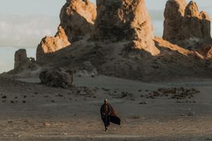 Man walking across desert, Trona Pinnacles, California, USの写真素材 [FYI03616876]