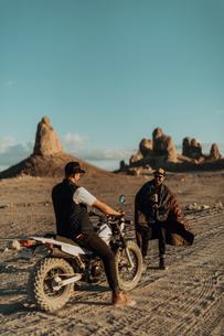 Motorcyclist friends talking on dirt track, Trona Pinnacles, California, USの写真素材 [FYI03616877]