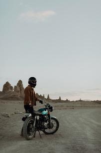 Motorcyclist beside stationary bike in desert, Trona Pinnacles, California, USの写真素材 [FYI03616879]