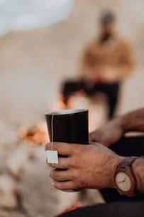 Friends enjoying cup of tea around camp fireの写真素材 [FYI03616883]