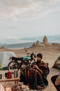 Motorcyclist road trippers around camp fire, Trona Pinnacles, California, USの写真素材 [FYI03616885]