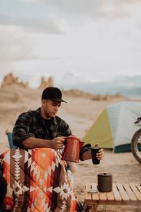 Man pouring hot water into mug, Trona Pinnacles, California, USの写真素材 [FYI03616886]