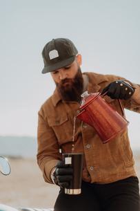 Man pouring hot water into mug, Trona Pinnacles, California, USの写真素材 [FYI03616895]