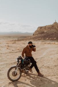 Motorcyclist enjoying drink on stationary bike, Trona Pinnacles, California, USの写真素材 [FYI03616897]