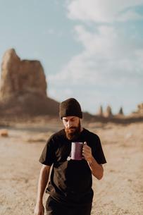 Man with mug of tea in desert, Trona Pinnacles, California, USの写真素材 [FYI03616898]