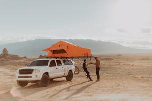 Motorcyclist friends taking break beside off road vehicle, Trona Pinnacles, California, USの写真素材 [FYI03616899]
