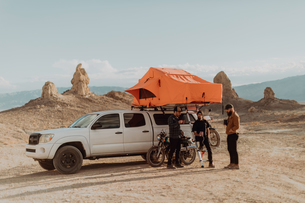 Motorcyclist friends taking break beside off road vehicle, Trona Pinnacles, California, USの写真素材 [FYI03616900]