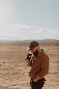 Man enjoying cup of tea in desert, Trona Pinnacles, California, USの写真素材 [FYI03616901]