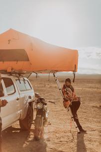 Motorcyclist beside tent admiring bike, Trona Pinnacles, California, USの写真素材 [FYI03616902]