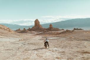 Motorcyclist riding in desert, Trona Pinnacles, California, USの写真素材 [FYI03616910]